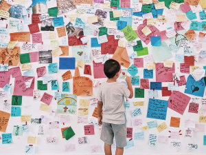 boy standing in front of wall of colorful notes